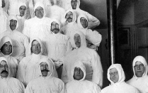 A group of adult men in head to toe white protective gear during the pandemic flu of 1918.