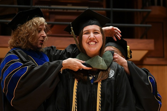 OT student Erin McDowell smiles proudly as she receives her hood during the 2017 ceremony.