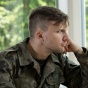 A depressed-looking member of the military looks out a window.
