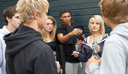 A group of teenagers smoking cigarettes and drinking alcohol.