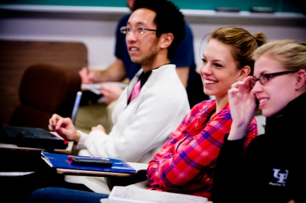 Students sitting and smiling in a classroom during lecture.