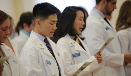students receiving their white coats.